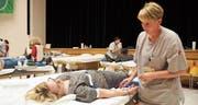 Fast wie im Spital: Im Uzwiler Gemeindesaal liegen Blutspender auf den Schragen. Nach der Blutentnahme gibt es zur Stärkung ein Brötchen. (Bilder: Angelina Donati)