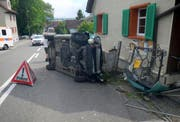 Das Auto kollidierte mit einem Gartenhag, einem Eisentor und einem Holzpfahl und kam auf der Seite liegend zum Stillstand. (Bild: KAPO)
