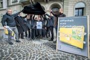 """Das Komitee für ein Thurgauer Öffentlichkeitsgesetz mit Initiant Ueli Fisch (ganz links) lüftet vor dem Regierungsgebäude ihre """"Blackbox"""" mit den gesammelten Unterschriften. (Bild: Reto Martin)"""
