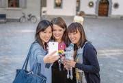 Als Touristenattraktion schlägt sie alle: Monstermama Clarissa Schwarz (Mitte) mit zwei chinesischen Touristinnen und drei Socken-Monstern. (Bild: Michel Canonica)