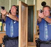 Die Hobbyschützen widmen sich schon der Gemütlichkeit, während die Polizisten René Stäbler und Kurt Marquart (von links) noch ihr Programm absolvieren. (Bilder: Mäx Hasler)