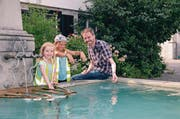 Viviane Keel (links) und Anouk Bucher kommen auf Michael Kontzen zu und planschen mit ihm im Dorfbrunnen. (Bild: Monika von der Linden)