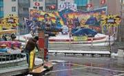 Kampf gegen das Wetter: Betreiber am Frühlingsjahrmarkt befreien ihre Bahnen vom Schnee. (Bild: Christoph Renn)