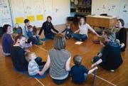 Musikpädagogin Esther Strässle (links vor dem Pult) singt mit Kindern unter vier Jahren und ihren Müttern im Schulhaus in Engelburg. (Bild: Ralph Ribi)