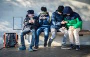 Die Blicke nach unten gerichtet, die Daumen glühen: die meisten Thurgauer Schulkinder besitzen ein Handy. (Bild: Reto Martin)