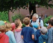 Die Kinder hängen an den Lippen von Rolf Zingg, der sie in St. Georgen durch den Wald führt. (Bild: Bettina Sieber)