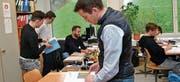 Ivan Louis (vorne) interessiert sich für das Lehrmittel Mathematik 2, während Lehrer Stefan Breitenmoser (Hintergrund) Schüler betreut. (Bild: Peter Jenni)