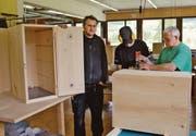 Marcello Pirrone (links) lässt seine Produkte für die Imkerei in der Schreinerei des Johanneums herstellen. Dort arbeiten der Berufsbildner Peter Lenggenhager (rechts) und der Schreiner-Lernende Renato Ammann an der Fertigung. (Bild: Jesko Calderara)