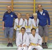 Die Trainer Andreas Kamber (links) und Daniel Federer mit den erfolgreichen Rheintaler Nachwuchs-Judoka. (Bild: pd)