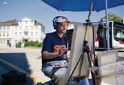 Unter dem Sonnenschirm und mit Kopfhörern malt Felix de la Concha derzeit rund um den Bahnhofplatz, wann immer es sonnig ist. (Bild: Coralie Wenger)