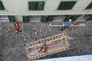 Christelle Wick und Hansruedi Kugler sorgen dafür, dass Fahrgestell und Aufbau des Lediwagens beim Transport in den Estrich des Bezirksgebäudes die Hauswände nicht beschädigen. (Bild: Martin Knoepfel)