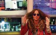 Kleine humorvolle Inszenierung mit der Sonnenbrille des Galeristen: Die Luzerner Künstlerin Irene Naef vor ihren Fotoarbeiten. (Bild: Martin Preisser)