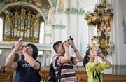 Familie Li fotografiert in der Kathedrale. Touristen aus China machen 1,5 Prozent der Logiernächte in der Stadt St. Gallen aus – Tendenz steigend. (Bild: Coralie Wenger (25. Juli 2014))
