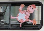 Toleriert: Das Fanmobil mit den vielen Fähnchen (oben) und die Kinderzeichnung auf dem hintersten Seitenfenster eines Kleinbusses.