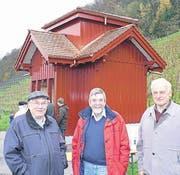 Die Rebbauern Bruno Zünd, Roland Coray und Jakob Ritz vor dem in neuem Glanz erstrahlenden roten Rebhüttli. (Bild: Ulrike Huber)