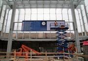 Arbeiter montieren über den Treppen der Rathausunterführung den neuen Bildschirm mit den Zugabfahrten. (Bild: David Gadze)