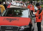 Nicht toleriert: Die grosse Fahne im Autodach (oben) und die Flagge auf der Motorhaube gefährden gemäss Polizei die Verkehrssicherheit.