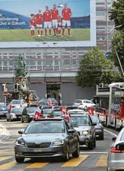 Euphorie in Rot-Weiss: Schweizer Fans am Samstag zu Fuss vor der «Union» sowie im Auto mit Werbeplakat einer Bank und Stadtbus auf dem Oberen Graben. (Bilder: Reto Voneschen)