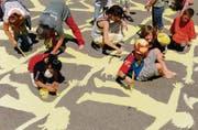 Sonnig ist es geworden: Die Fünftklässler des Schulhauses Riethüsli mit Pinsel und Farbeimern bei der Verschönerung ihres Pausenplatzes. (Bild: Coralie Wenger)