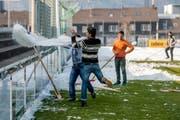 """Not macht erfinderisch: Flüchtlinge haben eine Abfallplache kurzerhand zu einer """"Schneewanne"""" umfunktioniert, um damit den Hauptplatz des Paul-Grüninger-Stadion von Schnee zu räumen. (Bild: Urs Bucher)"""