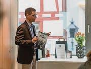 Claudius Krucker von Buchstadt St. Gallen zeigt einen Comic aus der Bibliothek, die hinter ihm in der Plexiglasbox zu sehen ist. (Bild: Kathrin Reimann)