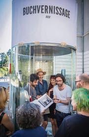 Claudio Bäggli (mit Hut), Soraia Simao, die Riklins und Gäste hören der Laudatio aus dem Mobiltelefon zu. (Bild: Urs Bucher)