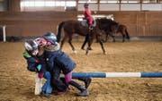 Wer gerade nicht auf dem Pferd reiten kann, stellt sich kurzerhand den Hindernisbalken als solches vor. (Bild: Michel Canonica)