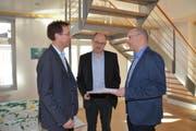Gemeindepräsident Roman Habrik nimmt die Unterschriftenbögen von Damian Kalbermatter und Thomas Feller entgegen (von links). (Bild: Beat Lanzendorfer)