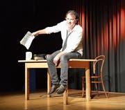 Stefan Waghubinger auf der Bühne in der Alten Turnhalle, in der Hand die Steuererklärung. (Bild: Nina Rudnicki)