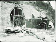 Arbeiter posieren neben einer Lokomotive vor dem Südportal des Bruggwaldtunnels. (Bild: PD/Staatsarchiv St. Gallen)