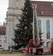 Der grosse Christbaum auf dem Klosterplatz muss weg: Die Feuerwehr sammelt am Montag den Schmuck ein. Und was vom Stamm der Tanne bleibt, nämlich zwei Meter lange Holzstücke, wird am Dienstag verladen.