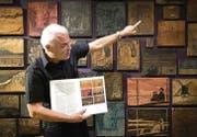Keine Farbdrucke, sondern Druckplatten zieren eine ganze Wand der Ausstellung. Museumsdirektor Daniel Studer erklärt die Technik. (Bild: Ralph Ribi)