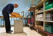 Ein Helfer entnimmt der Urne die Abstimmungscouverts. (Bild: Benjamin Manser)