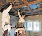 Sonja und Mauro Ferrari beim Restaurieren der freigelegten Barockdecke. Sie war mit zehn Schichten Farbe überdeckt. (Bild: zVg)