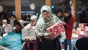 Freudestrahlend nehmen die Menschen im K-Treff die Geschenke entgegen, die Wittenbacher und Mörschwiler verpackt haben. (Bild: Ralph Ribi)
