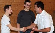 Rhodmeister Andreas Göldi gratuliert den beiden Jungbürgern Janik Egeter und Manuel Göldi zur ersten Teilnahme an einer Rhodversammlung. (Bild: Max Pflüger)