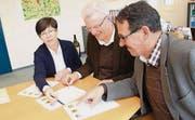 Die Gemeindepräsidenten Imelda Stadler, Karl Brändle und Toni Hässig diskutieren ältere Wappenentwürfe. (Bild: Martin Knoepfel)