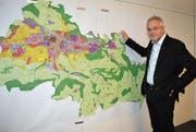 Gemeindepräsident Elmar Metzger zeigt auf den Ortsplan, der permanent im Sitzungszimmer des Gemeinderates hängt. (Bild: Urs Bänziger)