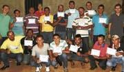 Die 14 Teilnehmer des Bauarbeiterkurses erhalten ihr Diplom: ihr Eintrittsticket in die Berufswelt. Im Hintergrund steht das im praktischen Kursteil errichtete Bauobjekt. (Bild: Leticia Sena)