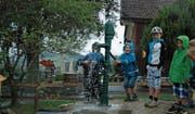 Ein paar mutige Kinder nehmen eine Dusche unter dem Wasserstrahl der neuen Wasserpumpe. (Bilder: Gianni Amstutz)