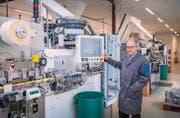 Permapack-Chef Thomas Hansmann und die neue Anlage zur Tubenproduktion. (Bild: Urs Bucher)