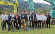 Martin, Wendel, Christof, Sepp und Andreas Giezendanner (mit Schaufeln, von links) vollziehen mit den Mitarbeitern und dem Vertreter der Bank den Spatenstich für die neue Werkhalle. (Bild: PD)