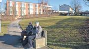 Zwei ältere Herren geniessen die Sonne im Park des Seniorenzentrums Sonnmatt. Das Areal in Niederuzwil ist rund vier Hektare gross. (Bild: Urs Bänziger)