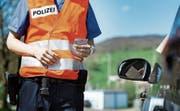Ein Polizist überprüft bei einer Kontrolle die Fahrzeugpapiere und den Ausweis. (Bild: Christian Beutler/KEY)