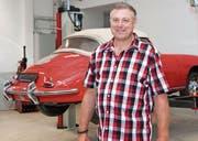 Andreas Hegelbach vor einem Porsche-Oldtimer in der Autowerkstatt von Kompass-Arbeitsintegration. (Bild: PD)