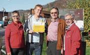Lucia Probst, Arthur Meier und Alfred Knüsel vom Verein Zuger Wanderwege überreichen Reto Scherrer das Schild. (Bild: PD)