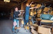 Andreas Günther und Martin Richard nehmen die Schulstühle vom Stapel runter. (Bild: Andrea Stalder)