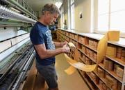 Erwin Tobler mit einer Lochkarte in seiner Werkhalle in Götighofen. Hier sticken historische Maschinen künftige Kunstwerke. (Bild: Helio Hickl)