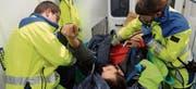Ein Patient wird mit starken Rückenschmerzen vorsichtig im Rettungswagen von Rettungssanitäter Adi Pfister und Lea Fischer für den Transport vorbereitet. (Bilder: Roland P. Poschung)
