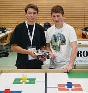 Kauê Manser und Remo Tobler mit ihrem Roboter vor dem Spielfeld. (Bild: pd)